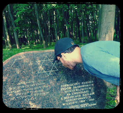 "Reading the memorial in the Jewish cemetery in Dąbrowa Białostocka. The Yiddish translates: ""The cemetery is all that remains of our beloved shtetl Dambrove, destroyed at the hands of the Nazis (may their names be wiped out). It will live on in eternal memory."""